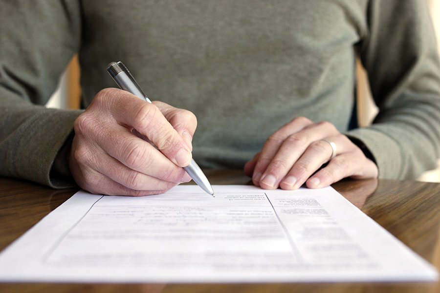 Add Lienholder Or Mortgagee - Man Sitting At Desk Filling Out Paperwork