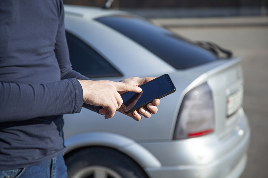Add Or Remove Vehicle - Man Standing Outside Next To His Car Using His Phone