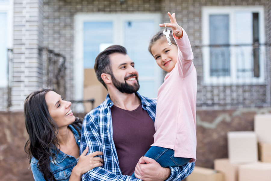Change Of Address - Smiling Parents With Daughter Holding Up Keys To Their New House