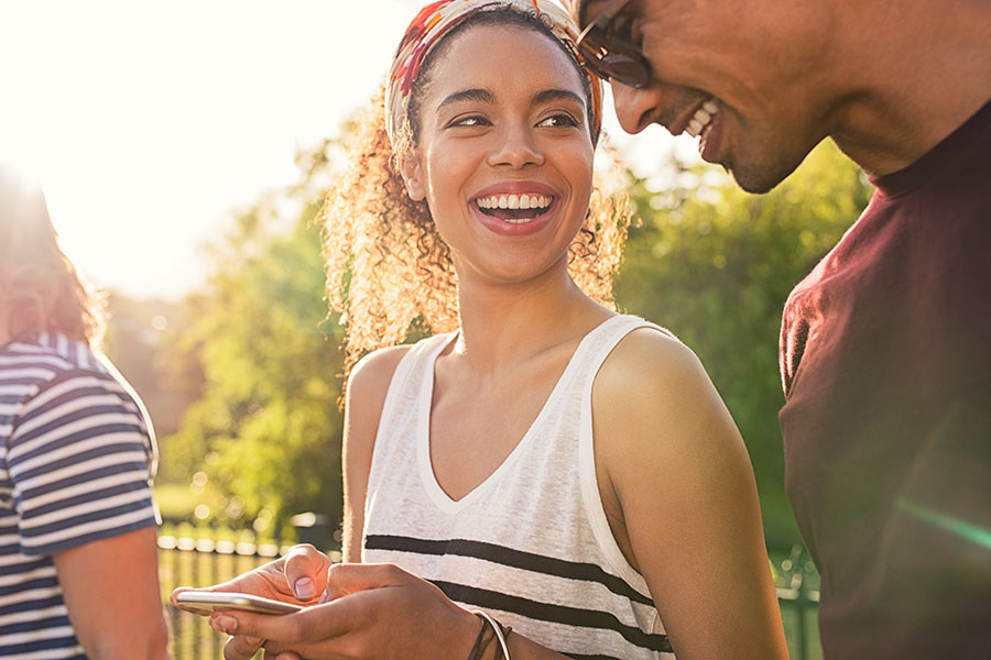 Client Center - Smiling Young Couple Standing Outside Using Their Phone