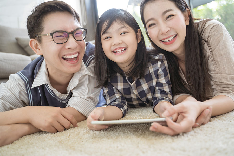 Video Library - Smiling Family Laying On Floor At Home Using Their Tablet Together